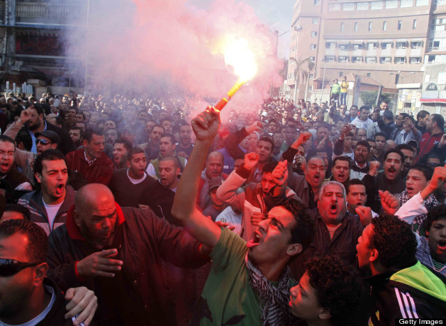 An Egyptian protester and fan of al-Masry football club waves a flare as others chant slogans during a demonstration in front of the prison in the Egyptian Suez Canal city of Port Said on January 25, 2013, calling for the prisoners who are suspected of killing 74 fans of al-Ahly club during a football match in February 2012, not to be transferred to Cairo to attend their trial. (Photo credit: AFP PHOTO / STR/Getty)