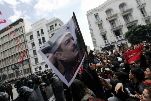 Tunisian protesters shout slogans during a demonstration outside the Interior ministry in Tunis on February 6, after the death of Tunisian opposition leader Chokri Belaid, pictured in the poster. (Photo credit: Anis Mili/ Reuters).