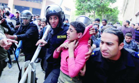 Egyptian riot police arrest a young man during clashes with protesters near Tahrir Square, Cairo (Photo credit: Associated Press).