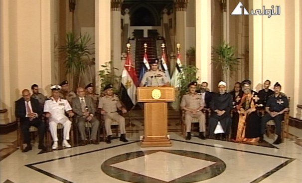 This image made from video shows Lt. General Abdel Fatah El-Sissi flanked by military and civilian leaders including reform leader Mohamed El Baradei, Tamarod leader Mahmoud Badr, Grand Sheikh of Al-Azhar, Ahmed El-Tayeb, and Pope Tawadros II, as he addresses the nation on Egyptian state television on July 3, 2013 (Photo credit: Egyptian State Television/Associated Press).
