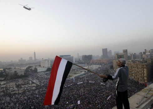 A military helicopter flies over a pro-military rally commemorating the Egyptian revolution's third anniversary (Photo Credit: AP/Amr Nabil)