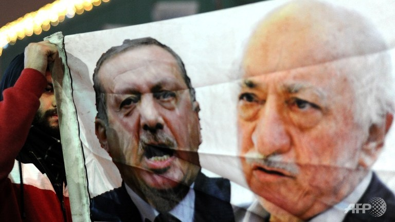 A Turkish protester holds up a banner with pictures of Turkish Prime Minister Recep Tayyip Erdogan (C) and Turkish cleric and head of the Gulen movement, Fethullah Gulen (R), during an anti-government and anti-corruption demonstration in Istanbul in December 2013. (Source: AFP/Ozan Kose)