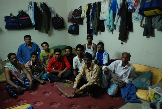 Photo featured in 2010 Human Rights Watch report, showing twelve men sharing one room in a labor camp, with no beds and no air conditioner. (Photo: Samer Muscati. Human Rights Watch. 2010)