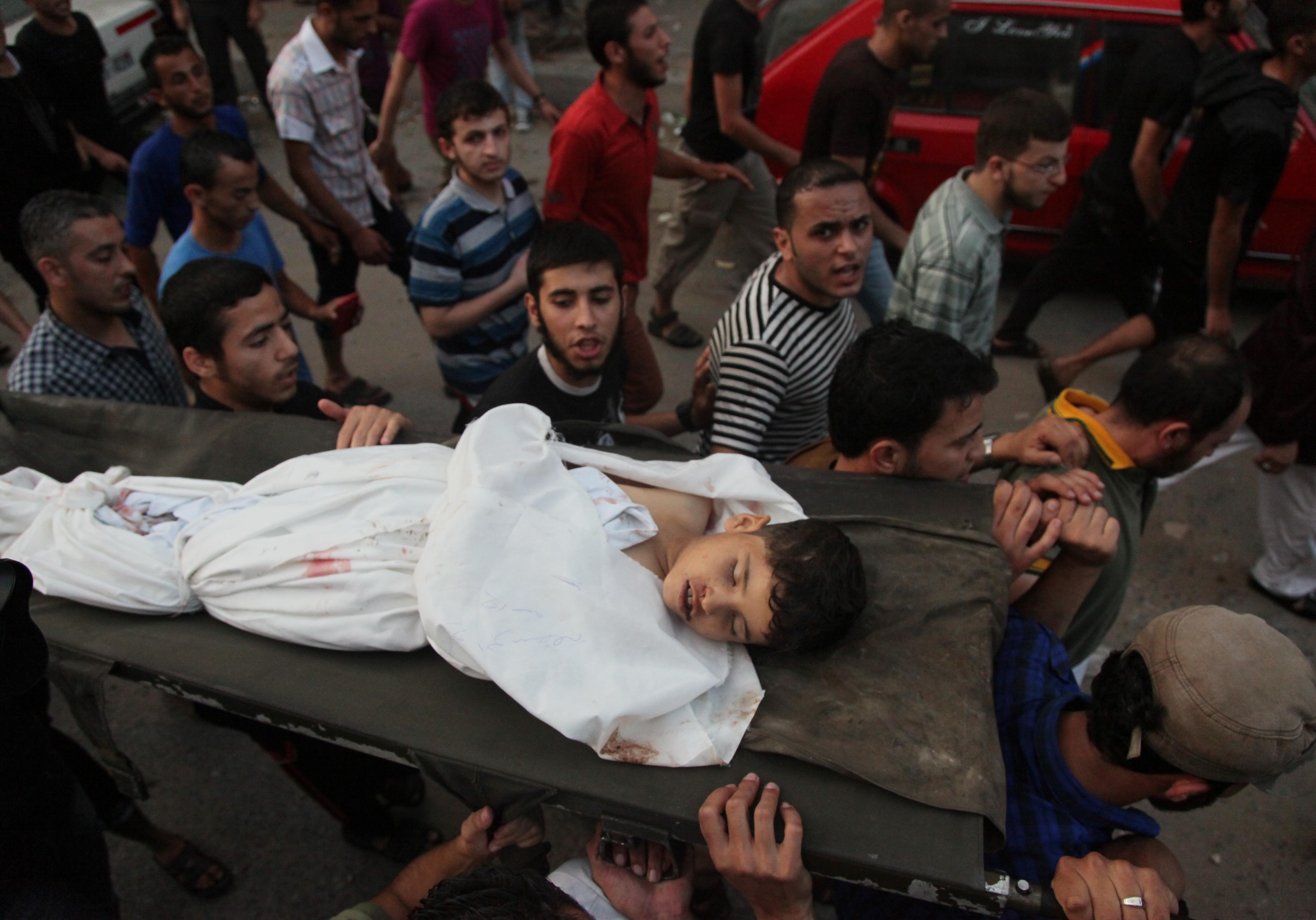 Palestinians chant slogans while carrying the body, who was killed along with 9 other people, all but one of them children, in an explosion at a park at the Shati refugee camp, in the northern Gaza Strip, Monday, July 28, 2014. At least 10 Palestinians are killed and more than 40 are injured in two Israeli airstrikes in the Gaza Strip, medics say, adding that most of the casualties are children. (Photo credit: Mohammed Zaanoun)