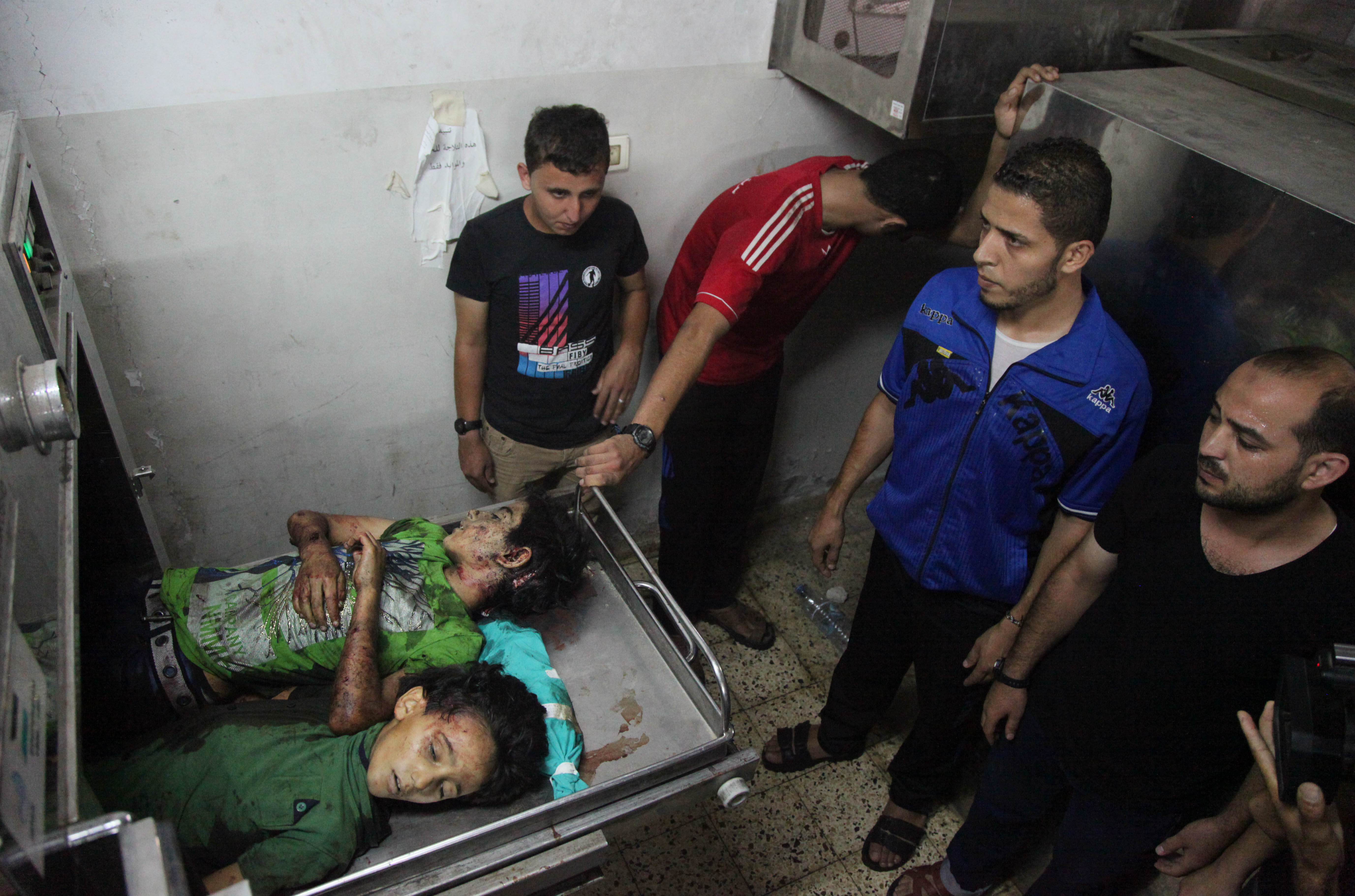 Palestinian men mourn over the bodies of six children who were killed in a explosion in a public playground in the beachfront Shati refugee camp in Gaza City on July 28, 2014. At least 10 Palestinians are killed and more than 40 are injured in two Israeli airstrikes in the Gaza Strip, medics say, adding that most of the casualties are children. (Photo credit: Mohammed Zaanoun)