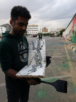 Ammar Abo Bakr with his sketchbook in Al Saidi Street, December 2013 (Photo credit: OMCT)