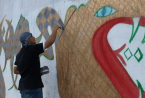 Ray-One working on his graffiti piece in Al Saidi Street, December 2013 (Photo credit: OMCT)
