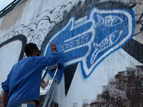 El Bohly working on his graffiti piece in Tripoli, December 2013 (Photo credit: OMCT)