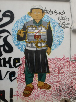 "El Bohly's graffiti piece in Tunis (Cinévog's wall) after completion in December 2014. It says, in Arabic, ""Explode your talents and help people around you"" (Photo credit: OMCT)"