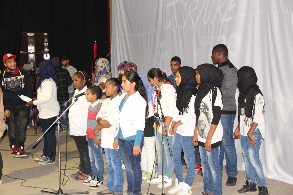 The young participants of the music workshop, on stage before performing the song they created for Human rights Day, December 2013 (Photo credit: OMCT)