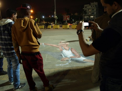 People gathering around Anas Mohammed and Mohammed Shandool's 3D graffiti piece in Martyrs' Square, December 2013 (Photo credit: OMCT).