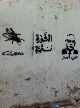 "Sektwo's graffiti piece in Tripoli, April 2013. It says in Arabic ""rebels"" (under the fly), ""the revolution continues"" in the middle, and ""who are you"" under the portrait of former Prime Minister Ali Zeidan, referring ironically to a sentence pronounced by Muammar Gaddafi in one of his last speeches. (Photo credit: Rebel group)."