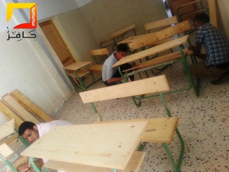 Young volunteers installing new furniture in a school, October 2013. (Photo credit: Montada Hafez)