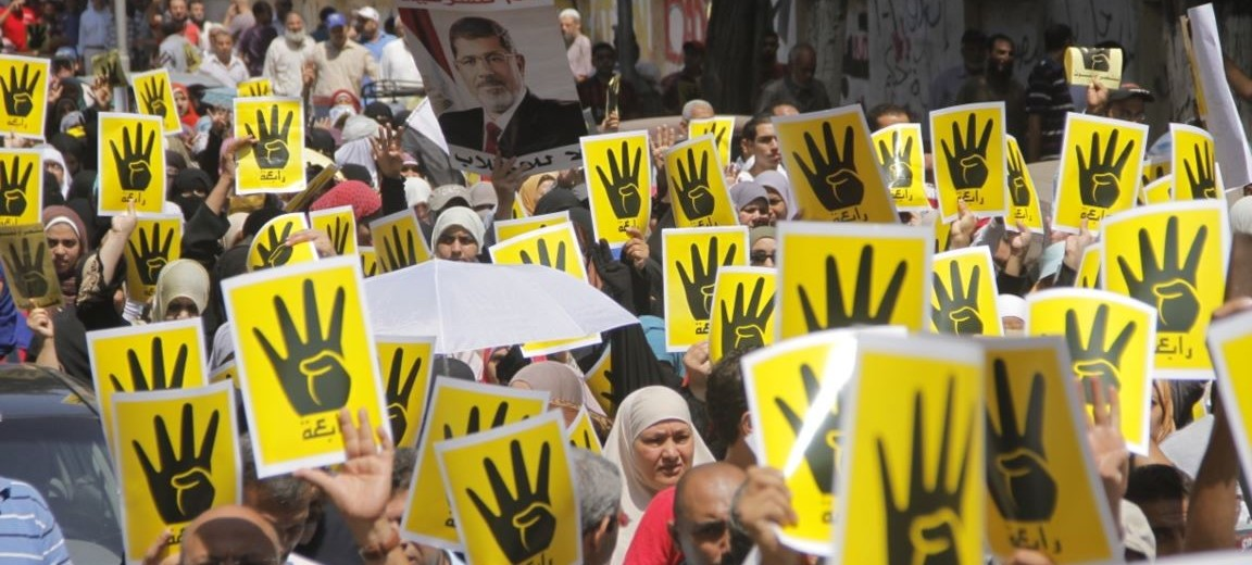 "Protesters hold the ""Rabaa sign"" in solidarity with victims of the massacre. Photo source: Wikipedia"