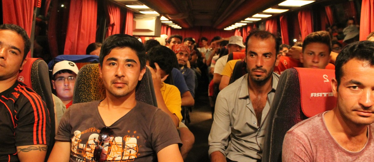 Syrian refugees, aboard the last bus to take off for the day, prepare to leave Molyvos for Mytilene