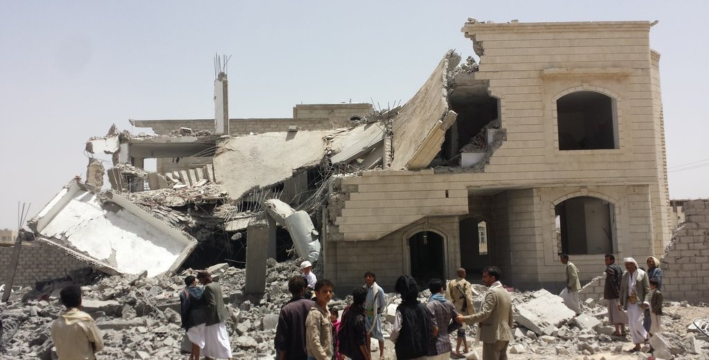 People stand outside a destroyed house in Sana'a after airstrikes