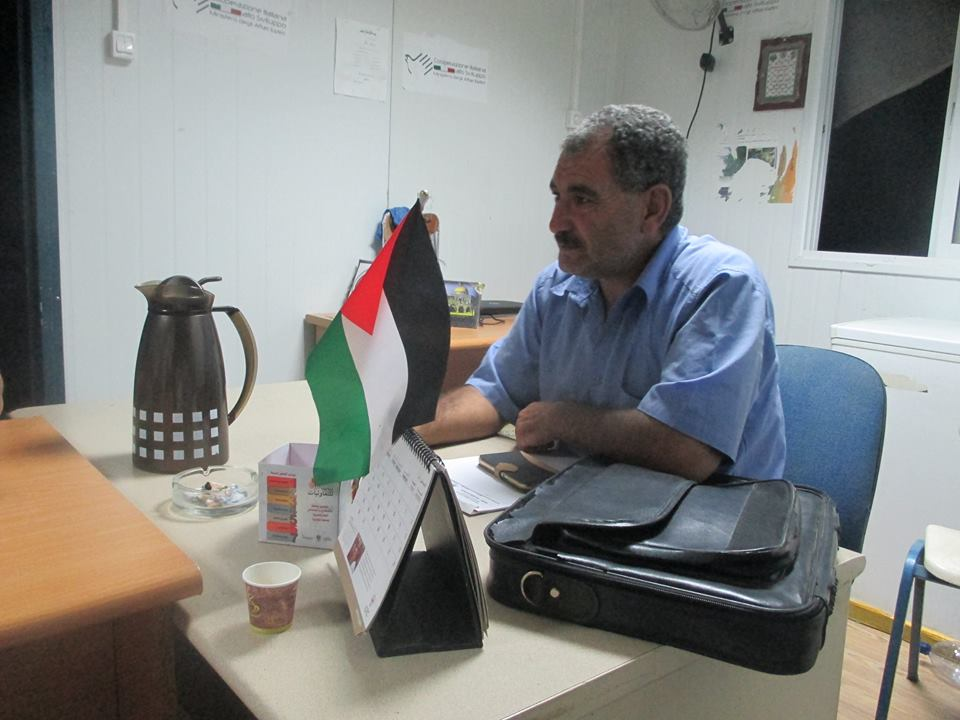 Jehad Nawaja, Susiya councilman and Nasser's brother, works in his office. Photo by Asad Dandia, June, 2015.