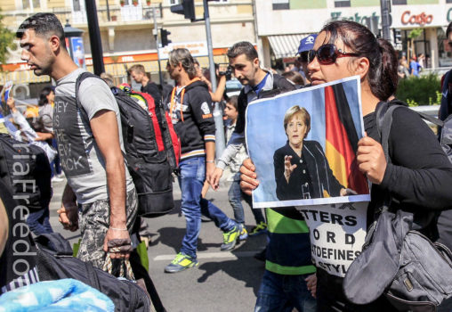 A woman holds a picture of German Chancellor Angela Merkel as migrants set off on foot for the border with Austria from Budapest, Hungary, September 4, 2015. Credit: Freedom House/Flickr